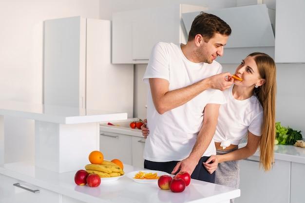 Casal brincando enquanto cozinha