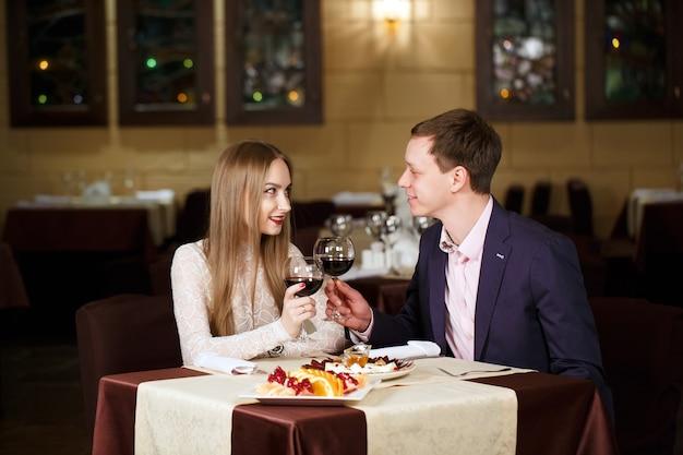 Casal brindando copos de vinho em um restaurante de luxo.