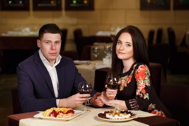 Casal brindando o copo de vinho em um restaurante de luxo.