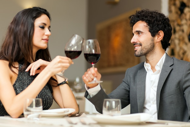 Casal brindando o copo de vinho em um restaurante de luxo