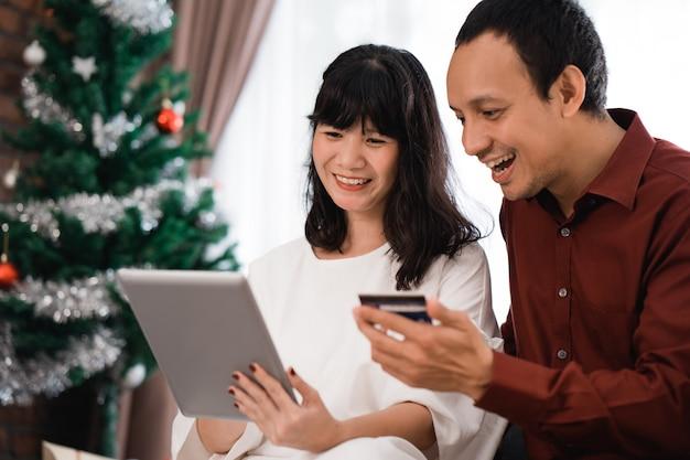 Casal caça negócio de venda de natal no mercado online. compras modernas usando cartão de crédito