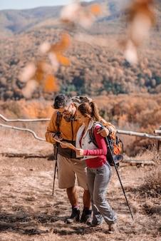 Casal caminhadas e olhando para o mapa.