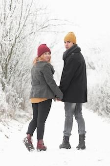 Casal caminhando ao ar livre no inverno e olhando para trás