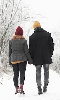 Casal caminhando ao ar livre no inverno por trás do tiro