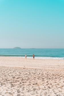 Casal caminhando ao longo da costa em uma praia ensolarada com um céu sem nuvens acima