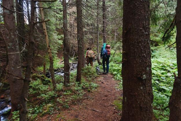 Casal caminhando com mochilas sobre fundo natural