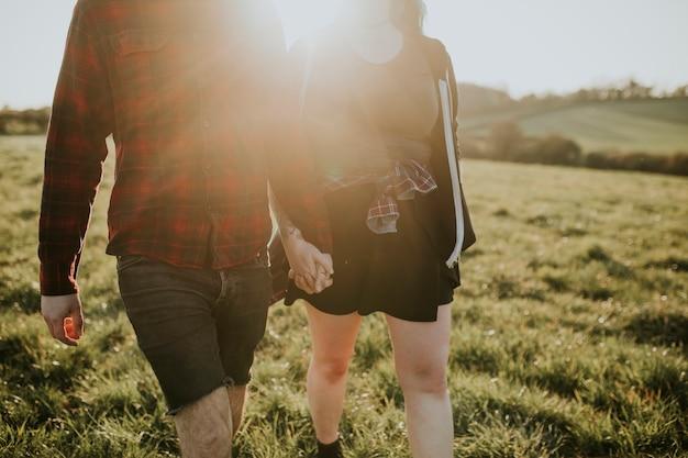 Casal caminhando e de mãos dadas ao ar livre