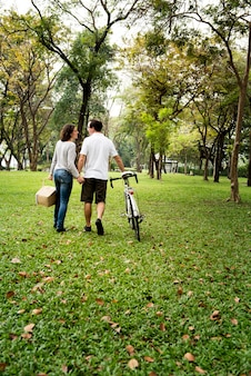 Casal caminhando e de mãos dadas no parque