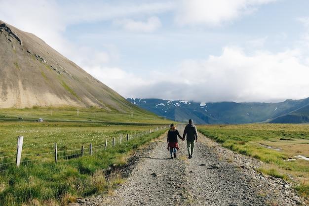 Casal caminhando em estrada de cascalho rural