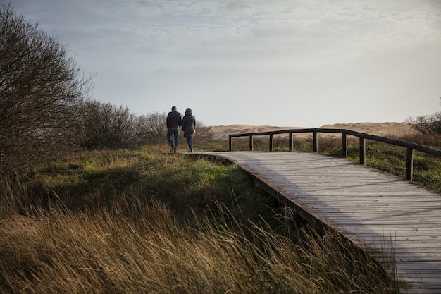 Casal caminhando em uma ponte de madeira cercada por um campo e colinas sob o sol
