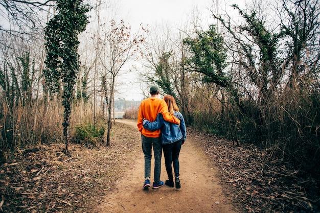 Casal caminhando juntos em trilha de cascalho na floresta