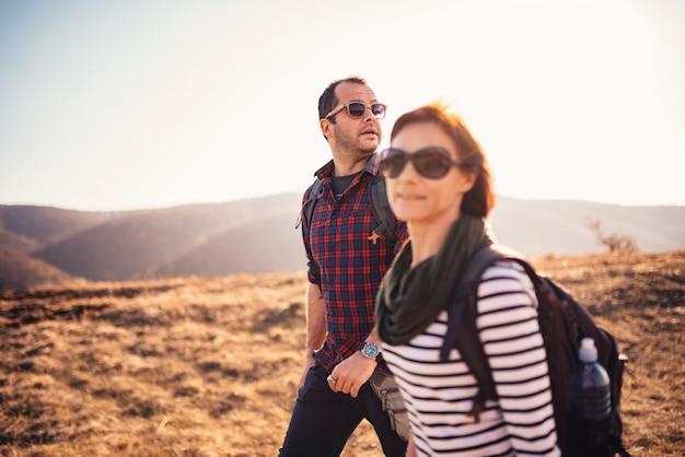 Casal caminhando juntos em uma montanha