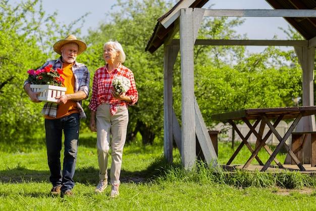 Casal caminhando. marido e mulher idosos e bonitos usando roupas casuais andando com vasos de flores