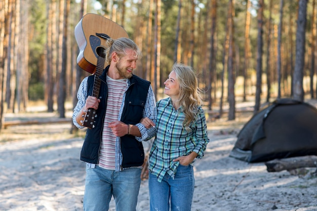 Casal caminhando na floresta com violão
