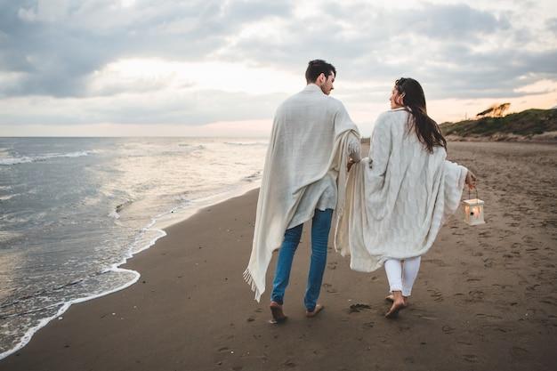 Casal caminhando na praia com uma vela