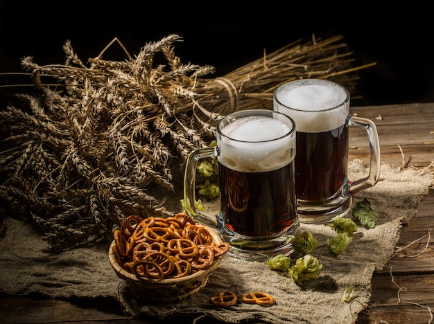 Casal caneca de cerveja com lúpulo e pretzels em pano de linho