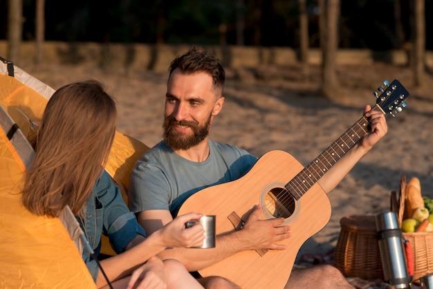 Casal cantando e olhando um para o outro pela tenda