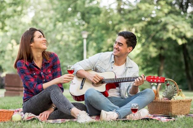 Casal cantando e tocando violão no parque