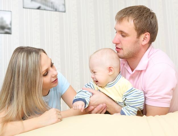Casal carinhoso deitado para acalmar o bebê irritado em casa