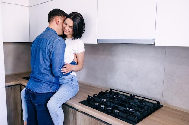 Casal carinhoso que fica em casa e abraços, mulher sentada à mesa da cozinha