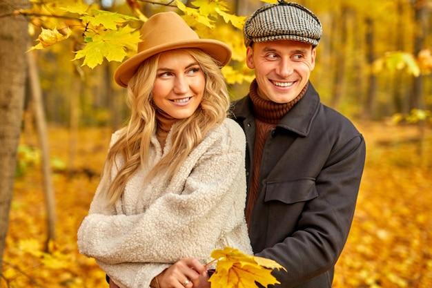 Casal casado com roupas estilo outono caminhando ao ar livre na floresta de outono