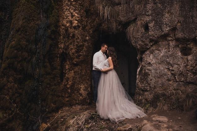 Casal casado com um homem e uma mulher grávida com uma grande barriga na natureza perto da montanha