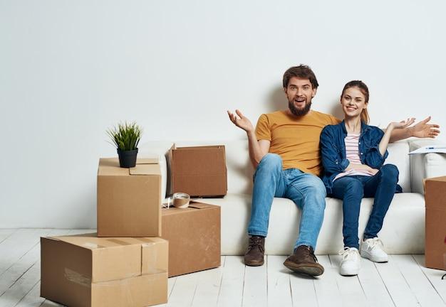 Casal casado em um sofá branco no interior da sala com caixas de coisas de comunicação