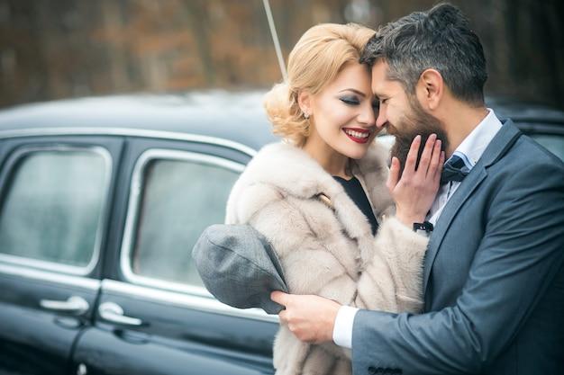 Casal casado no carro retrô preto em seu casamento.