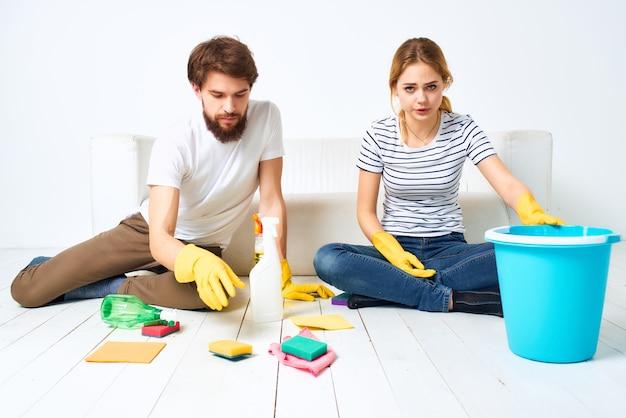 Casal casado perto do sofá trapos detergentes esponjas prestação de serviços