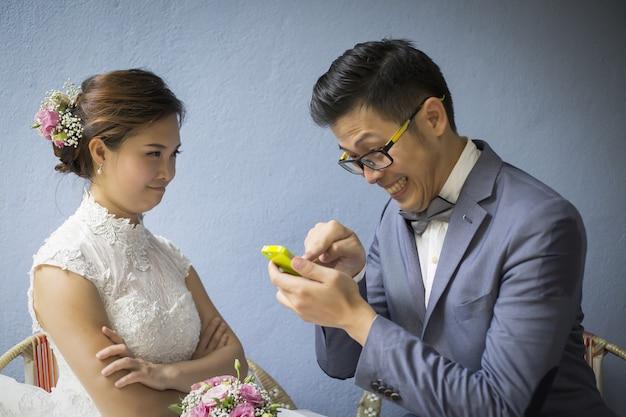 Casal casamento asiático amor, homem jogando telefone inteligente durante tirar fotos e mulher procurando seu namorado que se sente um pouco zangado.