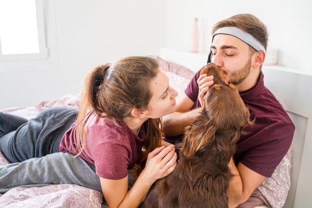 Casal caucasiano acariciando seu cachorro na cama. palma de maiorca, espanha