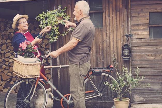 Casal caucasiano adulto aposentado fica no jardim em sua própria casa para trabalhar nas plantas e vegetais. bicicleta estilo antigo com eles