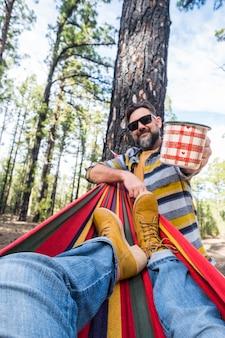Casal caucasiano adulto feliz aproveita a natureza, lazer ao ar livre, acampar - pernas de mulher na rede e homem em pé com café - férias no ambiente e na natureza