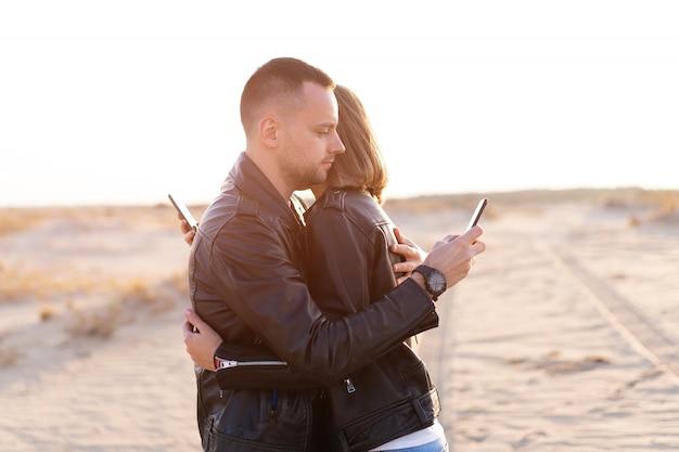 Casal caucasiano adulto jovem moderno com dependência de smartphone