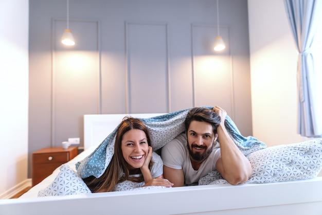 Casal caucasiano alegre e sorridente, deitado de bruços na cama e se cobrindo com lençóis