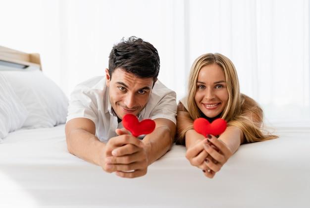 Casal caucasiano amante feliz sorrindo e segurando o coração vermelho nas mãos