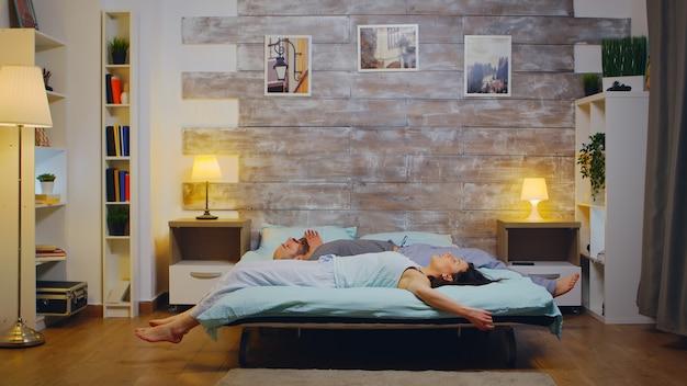 Casal caucasiano, caindo na cama de pijama após um longo dia de trabalho. foto em câmera lenta