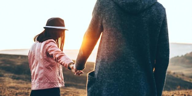 Casal caucasiano caminhando de mãos dadas em um campo durante uma noite ensolarada de verão