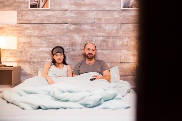Casal caucasiano de pijama assistindo tv deitado na cama aconchegante.