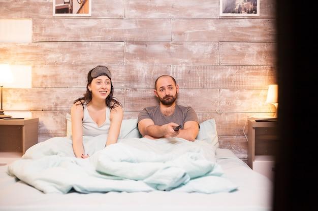 Casal caucasiano de pijama relaxando assistindo tv em uma cama confortável.