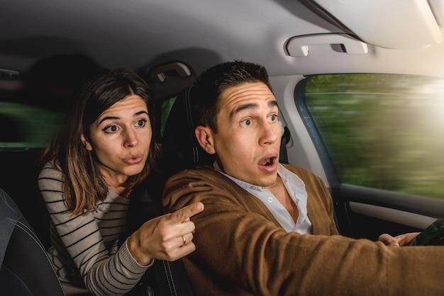Casal caucasiano dentro do carro em ação com fundo exterior desfocado.