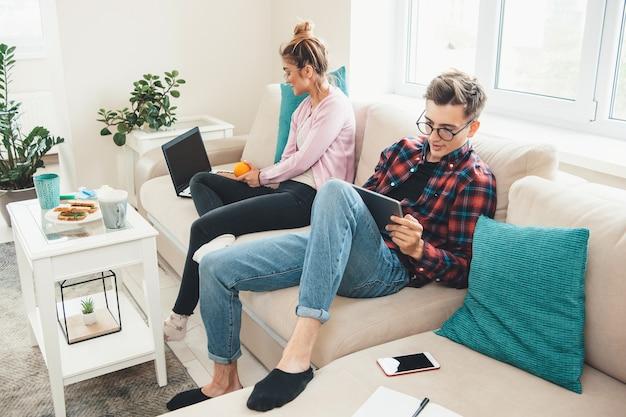 Casal caucasiano em casa sentado na cama a trabalhar no computador enquanto bebe um chá com sanduíches