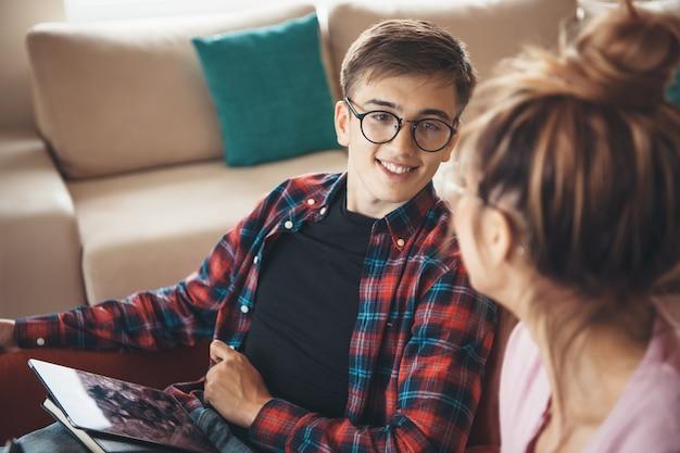 Casal caucasiano encantador com óculos discutindo e sorrindo enquanto usa um tablet