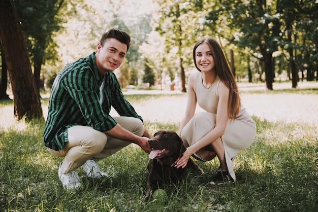 Casal caucasiano está brincando com cachorro