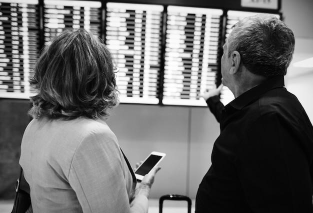 Casal caucasiano está verificando o horário de voo