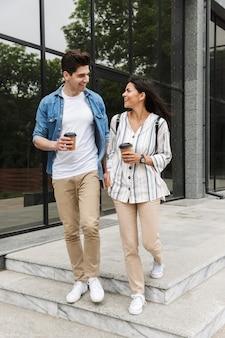 Casal caucasiano homem e mulher em roupas casuais, bebendo café para viagem enquanto passeia pelas ruas da cidade