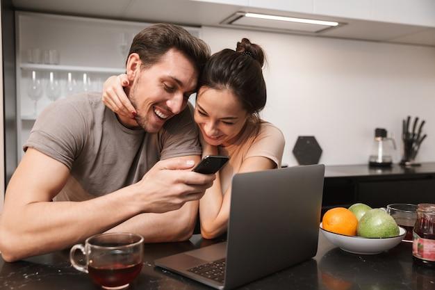 Casal caucasiano, homem e mulher, usando laptop com smartphone, enquanto está sentado na cozinha