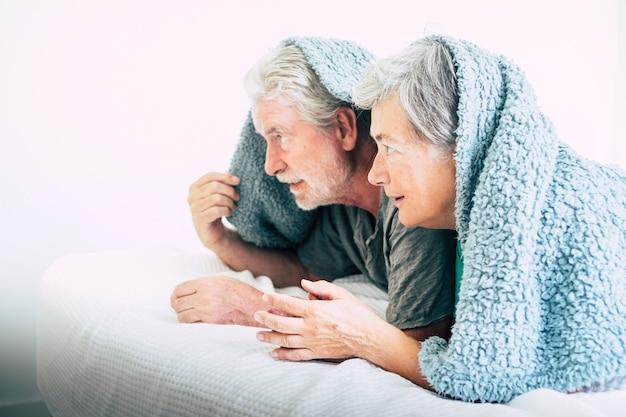 Casal caucasiano maduro brincalhão em casa jogando sob o cobertor na cama no quarto