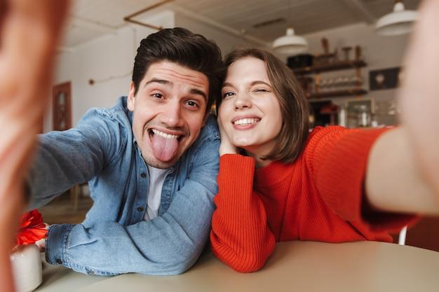 Casal caucasiano, mulher e homem sorrindo e mostrando a língua, enquanto tira uma selfie no café