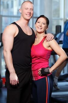 Casal caucasiano posando em uma academia
